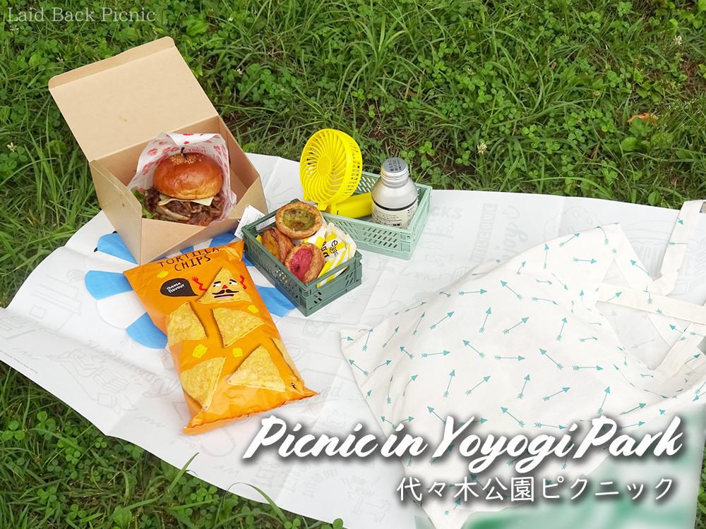 ピクニックシートに広げた、大きなハンバーガーやオヤツ