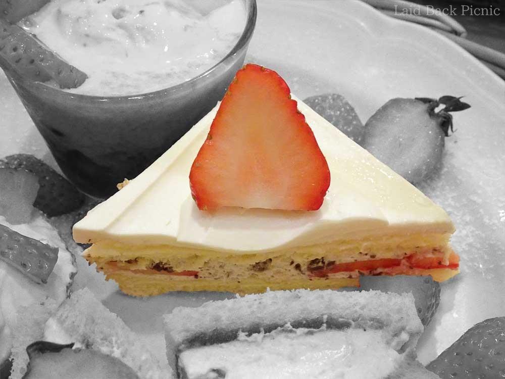 三角ショートケーキの上に、半分にカットした苺のトッピング