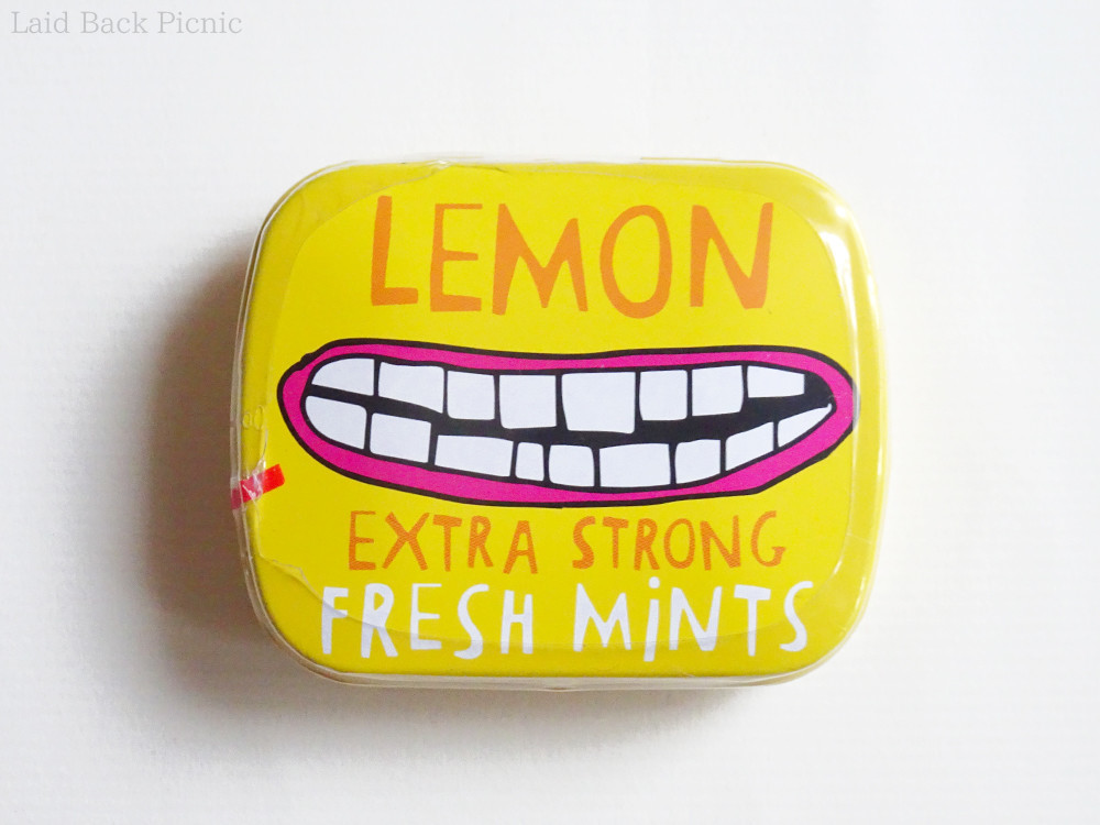 黄色い缶に、にーっと笑う口のイラスト入り