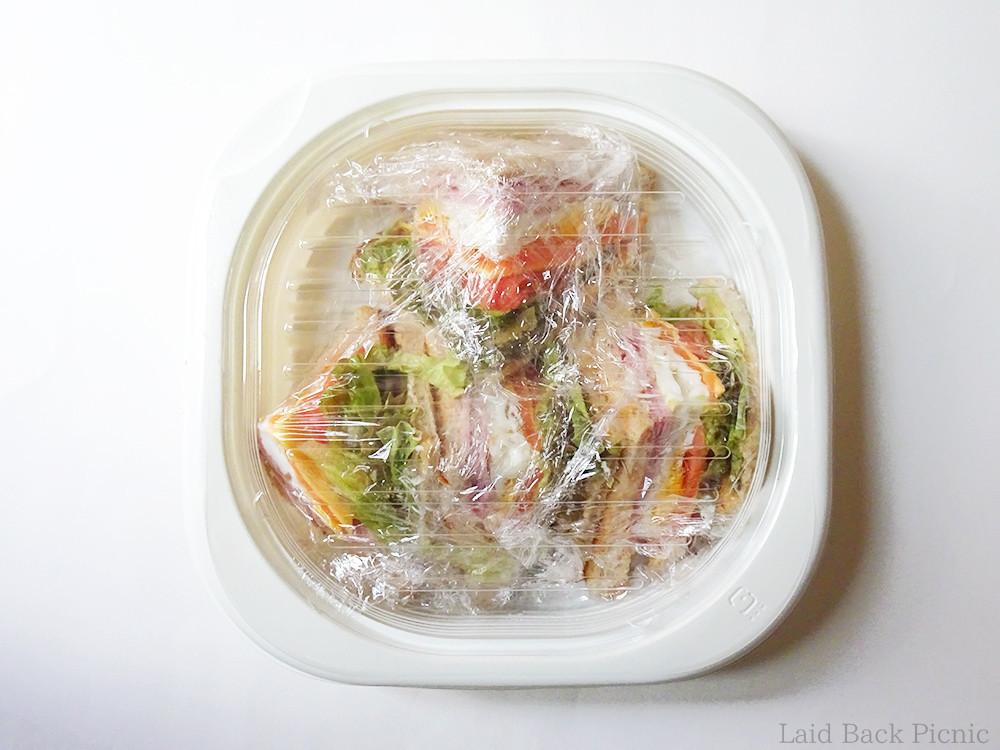 容器のなかでラップで包まれたサンドイッチ