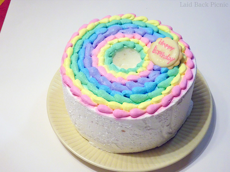 ピンクや黄色、水色、紫のクリームが上にたっぷり飾られたシフォンケーキ
