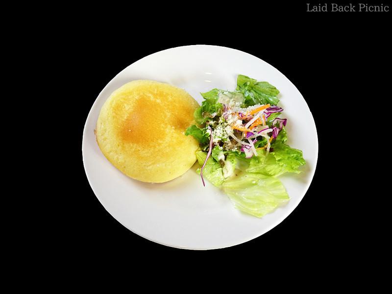 パンケーキ1枚の横にサラダが添えられている