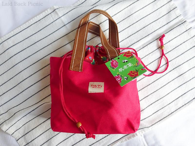 トートバッグは無地の赤色、上の方が客家柄の布で巾着のように絞れるデザイン