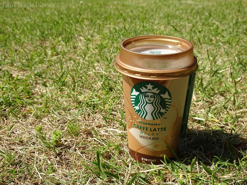 芝生の上にカフェラテを置いてのんびり楽しむ