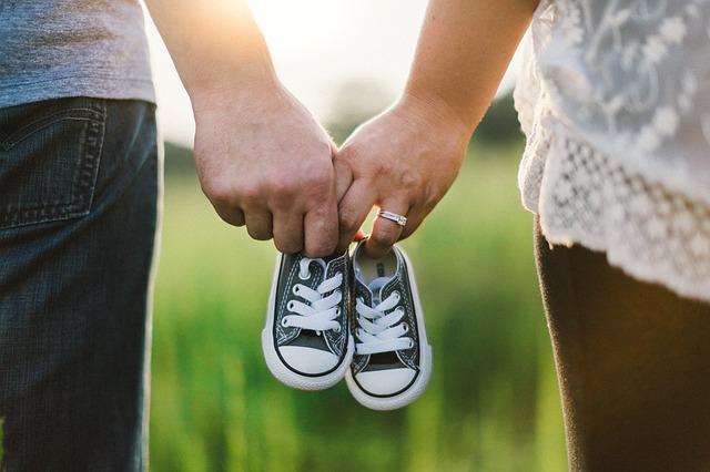 手をつないで子供の靴を持つ夫婦