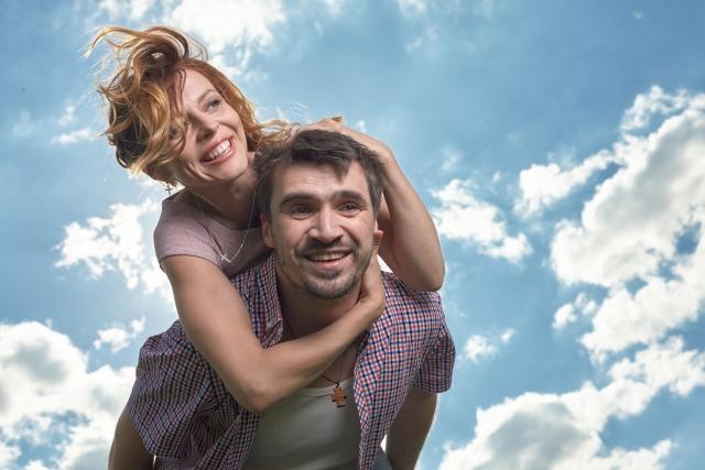 男性が女性をおんぶしている笑顔のカップル