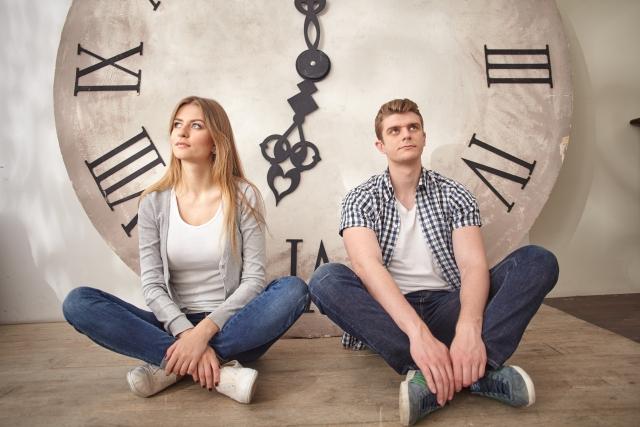 大きな時計の前に座る男女
