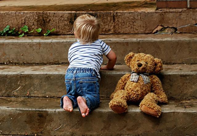 階段をのぼる少年とくまのぬいぐるみ