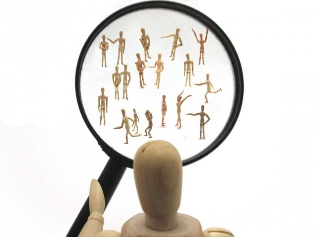 虫眼鏡で群衆をみる人の模型