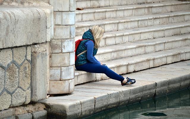 階段に座って落ち込む女性