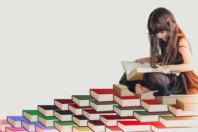 積まれた本の上で本を読む少女