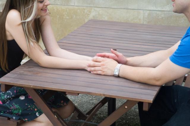 テーブルの上で手を重ねる男女