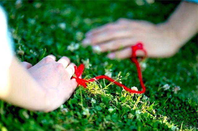 赤い糸で小指が結ばれた男女の手