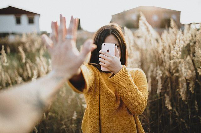 手を合わせて写真を撮る女性
