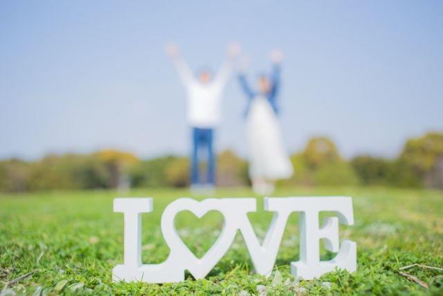 LOVEの文字と青空へ向かって手をあげるカップル