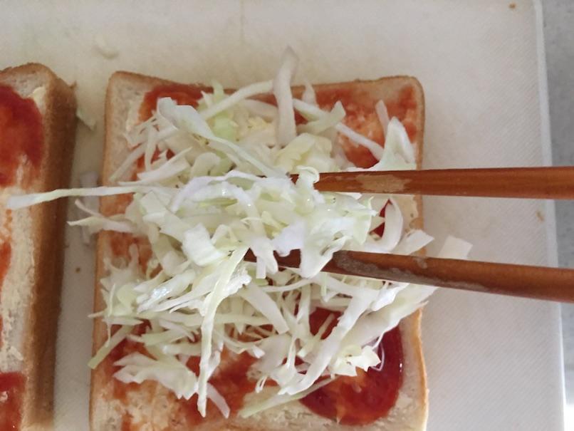トーストにキャベツを箸でのせる