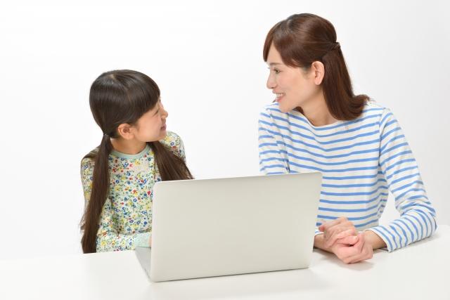 小学生が母親とプログラミング教育の体験をしている