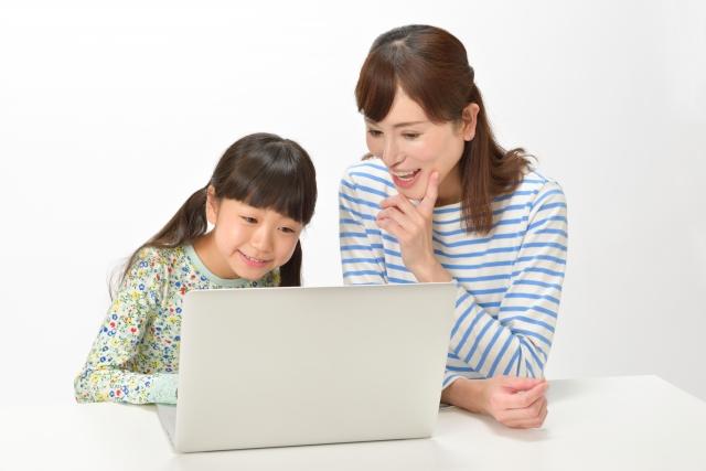 小学校1年生と母親がパソコンでプログラミング教育を受けている