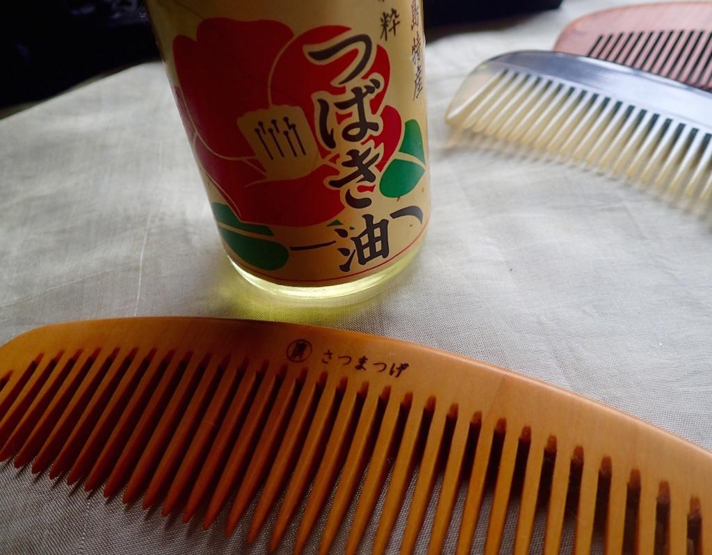 椿油の瓶とつげ櫛のクローズアップ写真