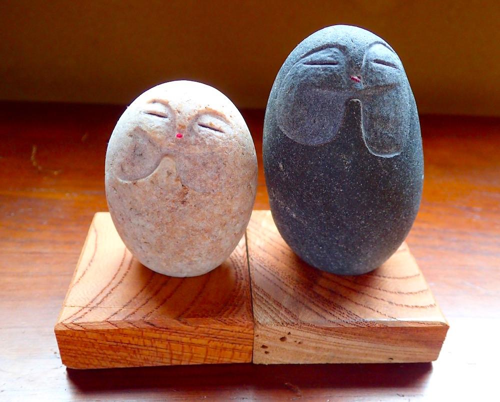木の台座に座った石彫りのふたつの縁結び地蔵さま