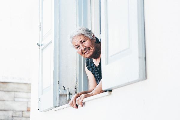 欧米人のお婆さんがにこやかに窓から顔を出している画像