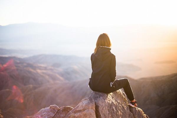 山の頂上に座る女性の写真