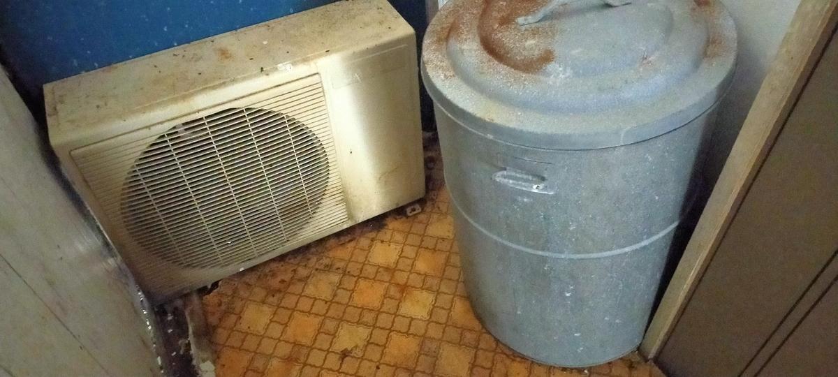 裏口廊下に置いてある壊れたエアコン室外機とゴミ箱