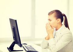 デスクトップPCの前で困惑している女性