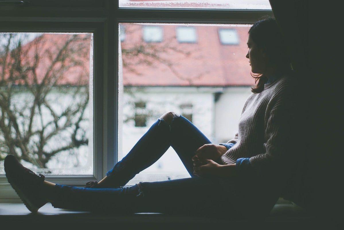 寂しげに窓の外を見る女性