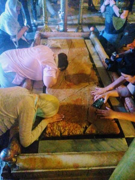 香油の注がれた石に触れるキリスト教徒