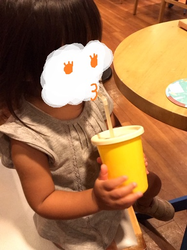 子供用のプラスチックコップとストローでジュースを飲む我が子