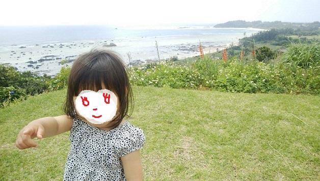 あやまる岬から見える海岸を背にした我が子