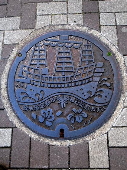 「政令指定都市移行記念」、南蛮船柄のマンホール蓋