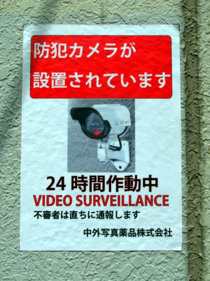 「防犯カメラが設置されています」との貼り紙。中外写真薬品株式会社のビル。