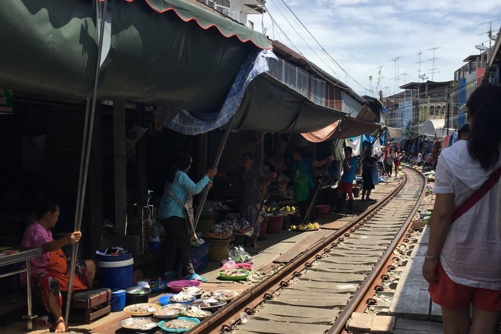 電車が通り過ぎて開店準備をするメークロン市場の人々