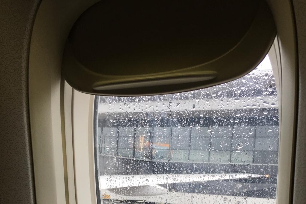 飛行機の窓から見る雨が降る空港