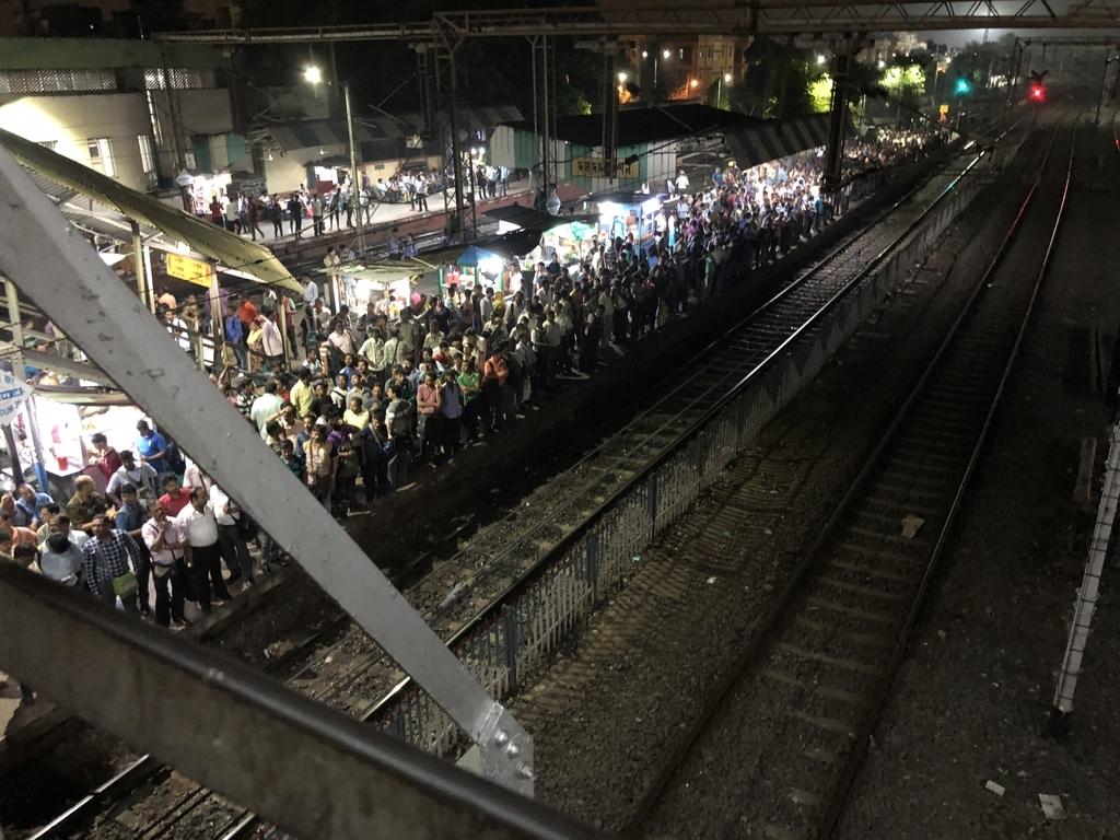 Dum Dum Junction駅のプラットフォームにたくさん人がいる光景
