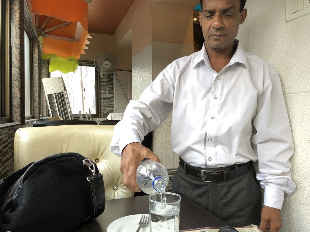 インドのウエイターの人がグラスに水を入れる