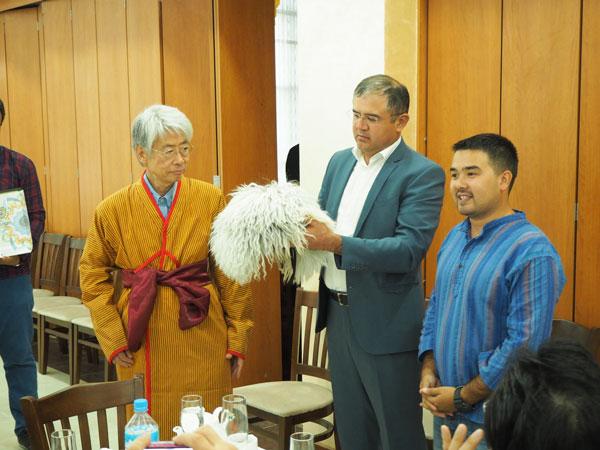 ウルゲンチ副市長から民族衣装を贈呈される嶌、現地ガイドのドストンさん(右)と