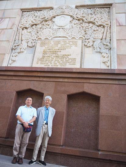 ナボイ劇場壁面の建築の功績を讃えるプレート前にて永田さんと嶌