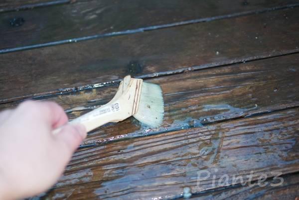 オスモウッドリバイバージェルを刷毛で木材に塗っている
