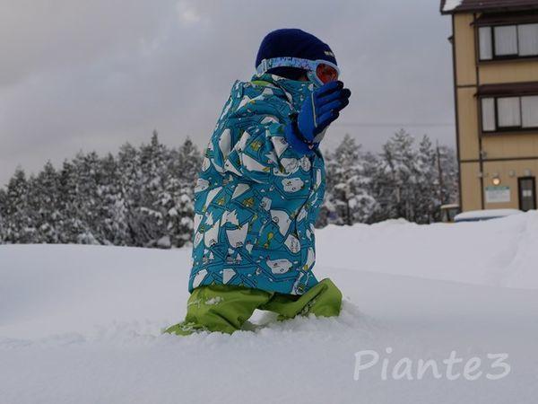 太ももまでの雪の中を歩く子供