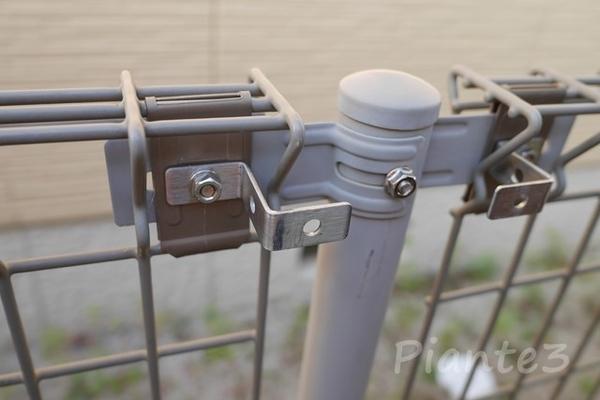 メッシュフェンス支柱にステーを共締めしている写真