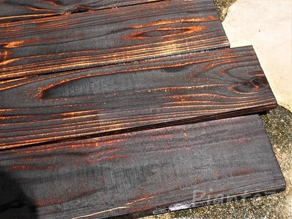 焼いた杉板を洗浄している写真