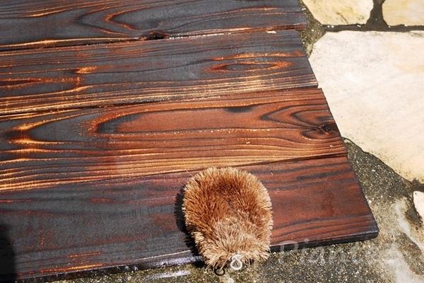 焼いた杉板をたわしで洗浄している写真