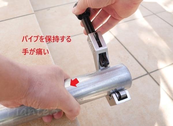 単管を切るときに手のひらで保持している写真