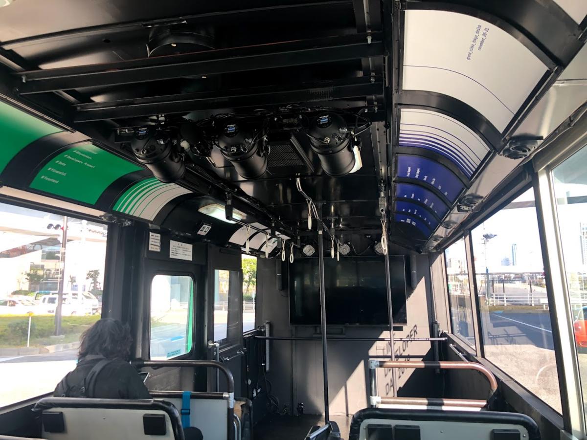 バス内装。座席含め全て黒塗りされ、正面にはディスプレイ装備。