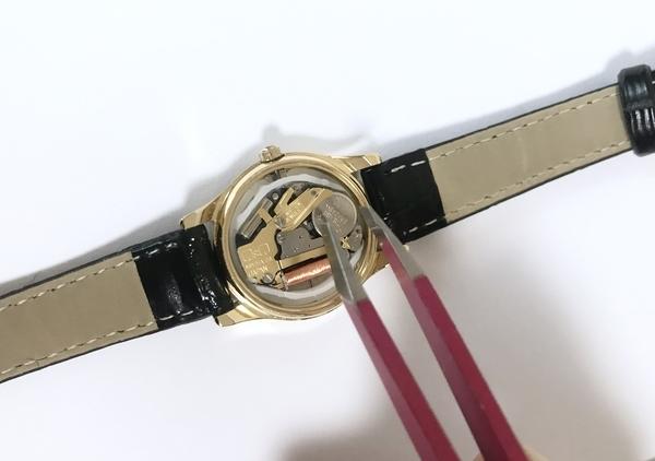 シチズン腕時計の使用電池をピンセットで取り出す画像