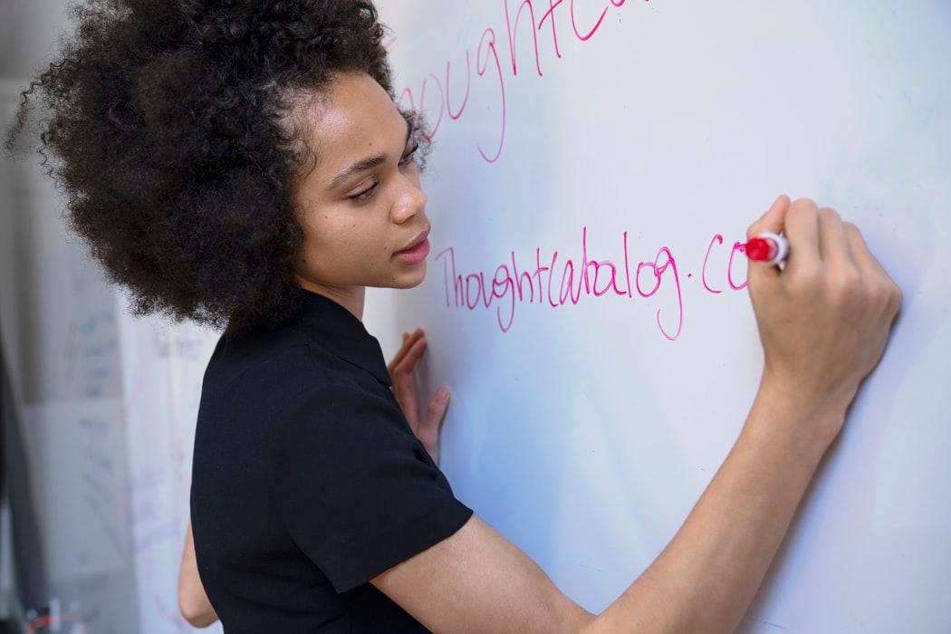 ホワイトボードで授業している女性