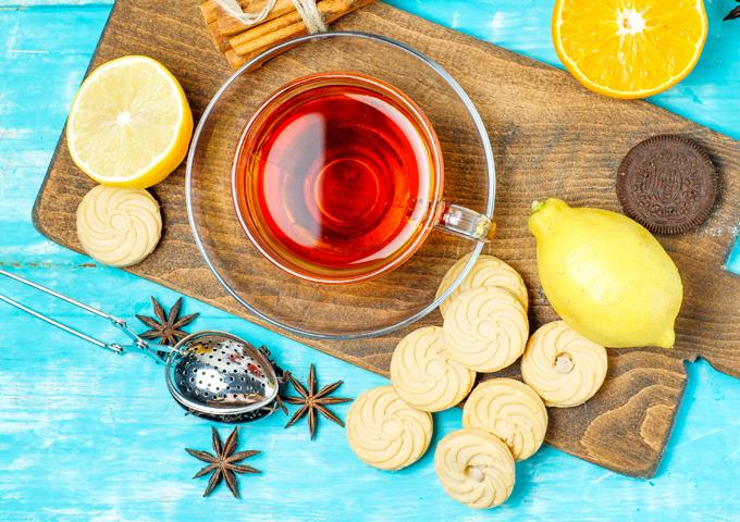 青とまな板の上のスパイス、紅茶、レモン、オレンジ、ストレーナーとビスケット